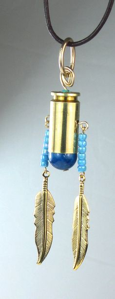 Cool bullet shell casing pendant with beads and gold plated dangling feathers.