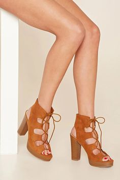 A pair of faux suede platform sandals featuring a lace-up front with an open-toe, a cutout back, and a chunky heel.