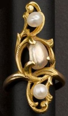 An Art Nouveau gold and pearl ring, featuring two baroque pearls and one round, mounted in unmarked gold.