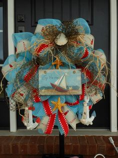 All About You Designs nautical deco mesh wreath with netting, anchors, starfish, lighthouse and nautical ribbons. BeautifuL!