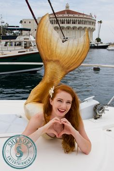 Redhead Catalina Mermaid smiling on Catalina Island at Avalon, California at the Pacific Ocean on a boat. This gold silicone mermaid tail beach beauty is a professional mermaid in Los Angeles who works with children at kids mermaid party events and in mermaid commercial work. Photo by Joe Woods, mermaid tail by Merbella Studios. Call (805) 328-4911 to hire a mermaid for your next pool party!