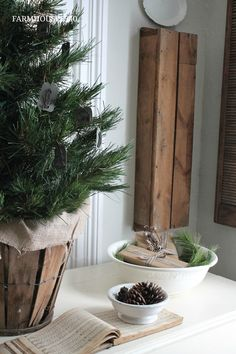 Table Top Christmas Tree Display - an artificial tree is wrapped in burlap and displayed in a vintage bushel basket. This is an easy way to add a rustic farmhouse look to your home - via Farmhouse 5540
