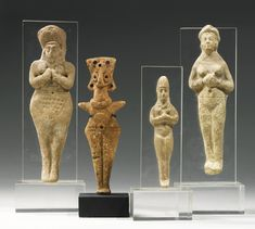 Four Terracotta Figurines, 2nd Millenium B.C. comprising a Syro-Hittite figure of a goddess of slender flattened form with short outstreched arms, wearing a notched girdle and applied collar, her bird-like face with large circular eyes and pierced coiffure, and three Elamite goddesses, each with hands held under breasts.
