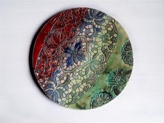 Large wall art plate with multicolored lace pattern for stylish design of interiors of home or of office. Diameter of the plate is 14,5 (=37 cm), weight app. 0,9 kg. The plate will get a hook on the back side, so that it can be easily attached to the wall. Each ceramic is unique by me, because I try to do all differenty. By the fact that its handmade it has a haptic style and that gives it an unique character. Each plate is singular and an unique. I am always looking for new desi...
