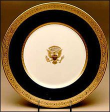 The Wilsons entered the White House in 1913,  By 1918, new china was needed.First Lady Edith Wilson preferred ordering American-made china,and chose Lenox after viewing a sample in a Washington, D.C. store.The Wilson pattern was designed by Lenox's chief designer, Frank Holmes, who chose a restrained theme The china featured a deep ivory border surrounding a brighter ivory body and two bands of matte gold encrusted with stars, stripes, and other motifs