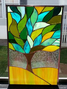 Stained glass window panel is made using various colors/textures of green glass as well as brown glass and clear frosted glass. it measures 10.75 wide by 16.5 long and is framed in a zinc channel metal frame ready to hang. will filter light and as you can see, the shades if glass change colors depending on what kind of lighting at various times of day.