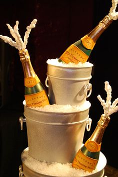 """Solid Chocolate Champagne Bottles with custom fondant labels sat on top of champagne bucket cakes with rock candy """"ice""""."""