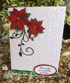 """http://calligraphycards-shazinoz.blogspot.com.au/2014/04/osa-using-artneko-stamps-sarns.html So embossed with CB Snowflake folder (disc.) and used holly ribbon from stash - have whole roll! Verse stamp is from Unity Itty Bitty """" For unto us a child is born"""" punched out with two oval punches from SU. I had two of these poinsettia made up on my desk for months now. It is a Britannia die and the leaf swirl from Memory Box."""