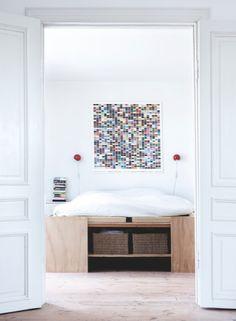 Desde el gran salón se abre las puertas  hacia el dormitorio. La cama de madera contrachapada tiene en su pie un espacio para almacenamiento...