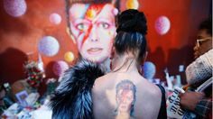 A woman with an Aladdin Sane tattoo visits a mural of David Bowie in London after the singer's death.
