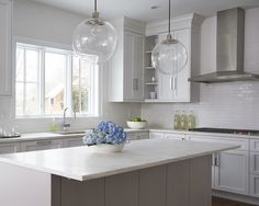 Calla McNamara Interiors  White Modern Kitchen, Grey Island, White Subway Backsplash, Glass Globe Lights  www.callamcnamara.com