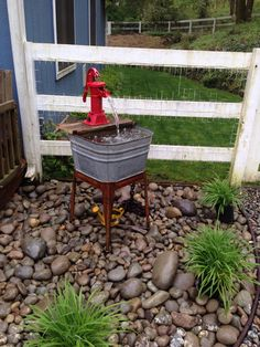 Fountain using old washtub, hand water pump, and old fence boards!