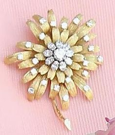 The Frosted Sunflower Brooch was made for the Queen by Garrard. It features petals made from 18 carat gold with a diamond center and diamonds studded on the petals.