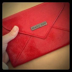 Mary Kay clutch NWOT small Mary Kay clutch. Eye-catching red color, material is smooth and shiny. Metallic closure, a wristlet strap can be attached from the inside (see pics). Mary Kay Bags Clutches & Wristlets