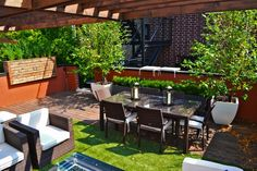 An outdoor dining table makes it easy to entertain under the stars and bright lights of Chicago on this urban rooftop deck. Ceramic planters and wooden container gardens offer privacy while adding a lively touch to the outdoor living space.