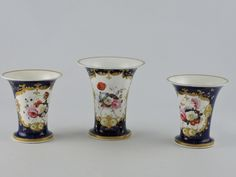 Lot 4 - A mid-19th century Coalport style vase, the central trumpet shaped vase with floral cartouche in a