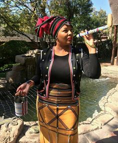 Xhosa lady in orange and black umbhaco skirt, red and black Doek, and umbhaco inspired sweater. African Print Dress Designs, African Print Skirt, African Print Dresses, African Dresses For Women, African Wear, African Fashion, Traditional Wedding Attire, Traditional Outfits, South African Traditional Dresses