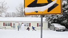 Becky McCurry plays in the snow with her kids Dolton and Michael Smith in front of their home on Denbigh Boulevard Thursday. (Photo by Rob Ostermaier / Daily Press)