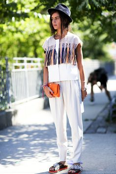 This street style star is giving us major hippy vibes and we're definitely liking what we're seeing! Her boho-eclectic look consists of a black hat, a contrast linen top with bright fringe details, a vibrant orange clutch, loose white pants and embellished slide sandals.