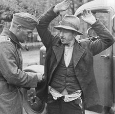 """A Romani (""""Gypsy"""") being searched. His disheveled appearance suggests that he was forced to pull his pants down to prove that he was not a Jew. (Poland around 1940.) [United States Holocaust Memorial Museum]"""