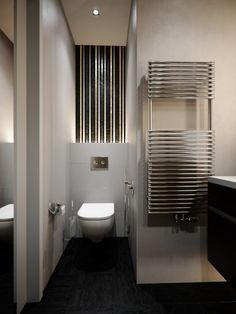 apartment bathroom contains white floating toilet, frameless bathroom mirror, modern towel's holder and basin shelves