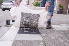 Berlin-based art collective Raubdruckerin(which translates to pirate printer)(previously) uses elements of urban design to create guerilla printing presses, adding ink to manhole covers, grates, and street tiles to create utilitarian designs on t-shirts and bags. The experimental print makers view