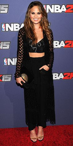 CHRISSY TEIGEN For the NBA 2K15 video game launch in N.Y.C., the model selects a bra top, toning down the sexy feel with a high-waisted skirt and sweater featuring sheer panels at the hem and sleeves.