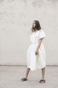 Structured, convertible kimono dress in white cotton grosgain. Wide cut silhouette with drop shoulders. V neckline; wraps across bodice and fastens with button