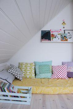 coin lecture avec le matelas du lit de bébé et des jolis coussins. Cagette peinte pour recueillir les livres.