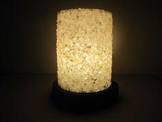Luminária redonda (27x35 cm) Superfície musiva realizada em técnica direta, utilizando pedras roladas semipreciosas (ametista, cristal e ônix) com acabamento misto (brilhante e opaco). Estrutura em madeira, acrílico e iluminação LED.