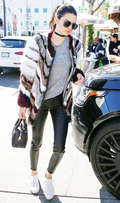 Kendall Jenner wears a gray t-shirt, patchwork fur coat, leather pants, white sneakers, a mini satchel, and a choker