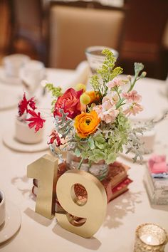 University of Wisconsin Fall Wedding, Low Floral Centerpieces with Gold Table Numbers and Vintage Books | Brides.com