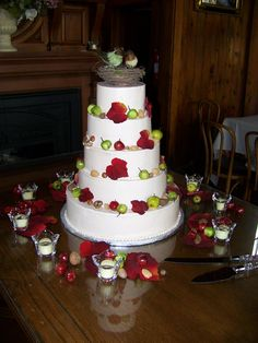 Simple wedding cake with apples and leaves.  Bird nest topper with love birds