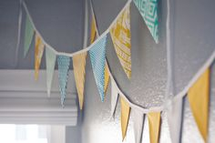 great idea from project nursery - Yellow, Blue, and White Pennant swags across walls.