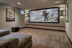 This transitional basement design has a simple theme; create a great movie watching experience in a small space. This basement has a large home theater with tons of hidden storage, built-in bookcases and an extra bathroom; all perfectly contained in a small basement.