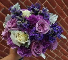 """... this bouquet has two different shades of the new Florigene Moon Series Carnations, selecting """"Moonshade"""" and """"Moonligh""""t, and added """"purple larkspur"""", """"blue curiosa roses"""", """"ivory roses"""", and """"dusty miller""""."""