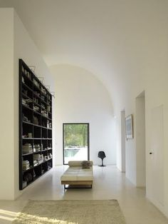 White Plaster, Black Bookcase (wood?), Warm Concrete Floor (Polished?), Simple Forms, Metal Windows