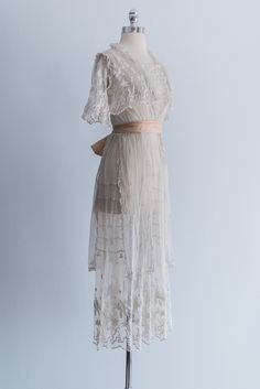 - Overview - Care - Shipping - DESCRIPTION: 1910's Edwardian lawn dress with built-in bolero, ruffled front and features embroidered lace skirt with front and back panels. Snap closures in the front.