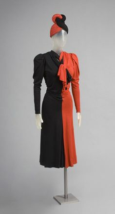 This is what 40s fashion was best at. the effect of parti-colored red and black sinuous silk jersey extends from the hat, with its twisted topknot, to the dress, in which clever pleating onto tapes eliminates the waist seam and drapery is interlaced at the neck.