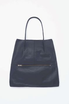 Made from lightly textured raw-cut leather, this versatile bag can be worn as a large tote or folded over and worn over the shoulder using the slim detachable strap. A rounded shape, it has a simple inside compartment and an outside zip pocket for smaller belongings.