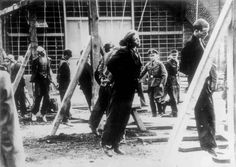 Soviet forced laborers swing from the gallows courtesy of the SS at the Cologne-Ehrenfeld concentration camp on Oct 25, 1944. Death was the usual penalty for even the slightest infraction. Note how the young man in the center of the picture has his eyes open looking at the last sight of his life as the rope robs him of his breath.SS officers observe in the background.