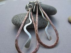 A simple artisan piece for everyday use. I hand forged and hammered the copper wire to get this drop shape and in the middle I attached a sterling silver wiggle to add a little sophistication. At the end I tarnished and hand polished the pieces to get a rustic and antiqued look. I applied a clear coat to protect the tarnish and your skin of getting dark. The ear wire is also hand forged by me using Sterling Silver wire. Enjoy them!   Dimension: -total length is 2 3/4and the drop part is ...