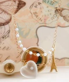 A frosted white vintage lucite heart with a sparkling rhinestone attached, dangles from a golden tone chain and is adorned with a tour eiffel golden charm and a shorter vintage chain with tiny white glass pearls.