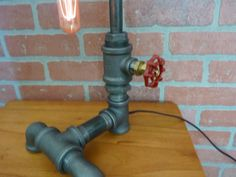 Our tube lamp. Features our exclusive one of a kind faucet handle dimmer - you turn the handle to control the flow of electricity and brightness of the light, a truly amazing feature which really adds to the uniqueness and functionality of the lamp! Lamp stands 17 inches tall, includes a 60 watt antique style 7 tubular bulb rated to 3,000 hours and 8 ft. long brown cloth covered cord. All lamps ship out within 72 hrs, securely packed in foam via UPS from AZ or CO. All lamps made with brand…