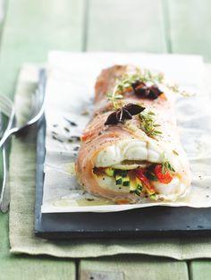 bereiden: Verwarm de oven voor op 180°. Snijd de courgette en zongedroogde tomaatjes in fijne reepjes. Schil de citroen en snijd in fijne plakjes. Leg de plakjes ham overlappend op elkaar. Leg daarop een filet van zeewolf. Beleg met de reepjes courgette, fijngesneden zongedroogde tomaten en citroen. Kruid met versgemalen peper en olijfolie.