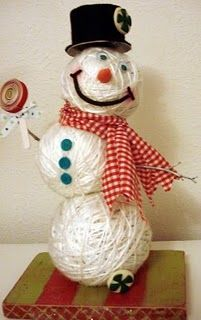 Syrofoam balls wrapped in yarn and sticks & scarf added to make snowman. (*His hat could be a ribbon roll with bottom pulled off.)