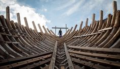 A Buginese man holds a hammer as he starting to work to install a wooden block in the hull of phinisi at Tanjung Bira Beach on May 2, 2014 in Bulukumba, South Sulawesi, Indonesia. Phinisi, a masterpiece of traditional Bugis-Makassar design, is a traditional wooden two-masted sailing ship, well-known as traditional sea transportation amongst the buginese people for many centuries. According to the ancient I La Galigo manuscript, phinisi has already existed since around the 14th century.