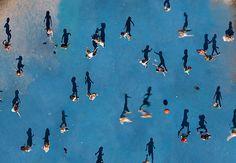 L'ombra e il corpo.  (Strepitosa immagine di persone come punti e ombre come persone: siamo ad Amsterdam, nel cortile di una scuola all'ora di ricreazione).  Ph: Katrin Korfmann
