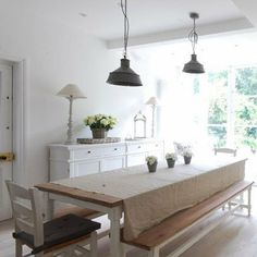 White dining room with wooden table and white table cloth
