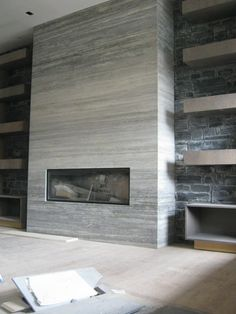 Modern Tile Fireplace with floor to ceiling shelves on both sides.